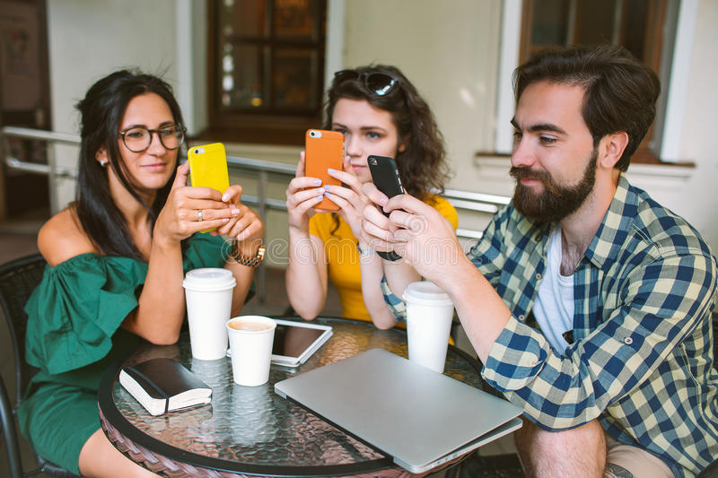 Young friends with smartphones and laptop in cafe with coffee stock images