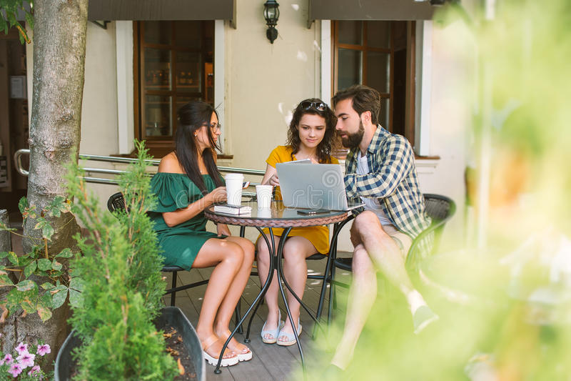 Young friends with smartphones and laptop in cafe with coffee royalty free stock photos