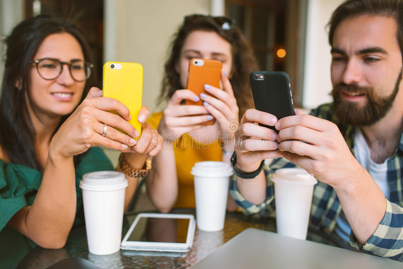 Young friends with smartphones and laptop in cafe with coffee stock photos