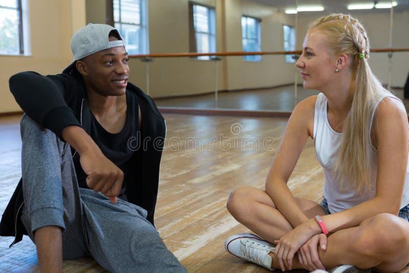 Friends talking in dance studio. Young friends talking while relaxing on floor in dance studio stock image