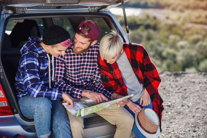 Young friends travelers sitting on trunk of car and looking at the paper map. Hipster happy tourists enjoying on royalty free stock images