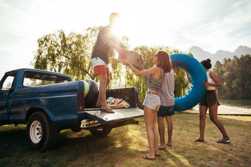 Young friends unloading pickup truck on camping trip royalty free stock photo