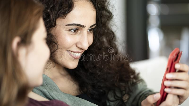 Young friends using mobile phone at home. Young friends using mobile phone  at home stock photography