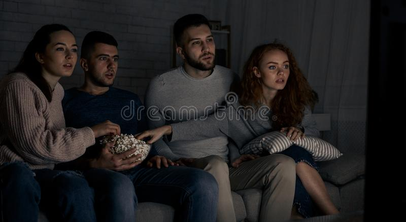 Young friends watching interesting film at home royalty free stock images