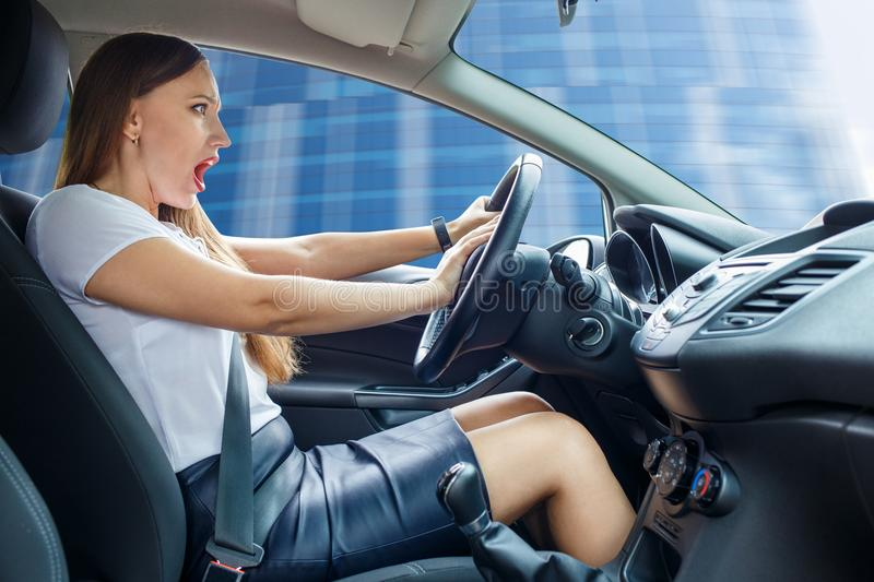 Young frightened driver woman squealing brakes stock photo