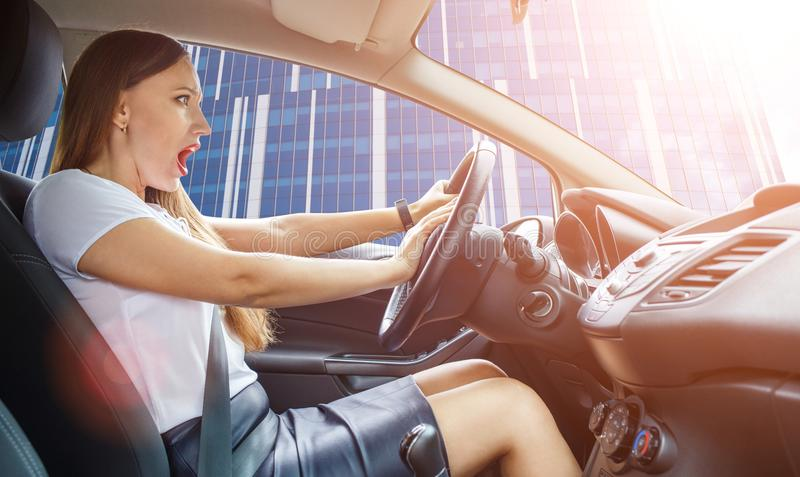Young frightened driver woman squealing brakes. In traffic jam stock photo