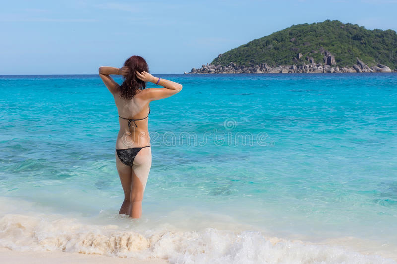 Young in front of blue sea. Young woman standing in the water in front of blue warm sea royalty free stock image