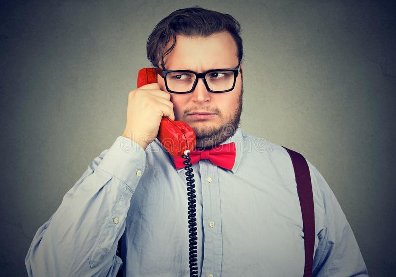 Frowning man having problem while speaking on red telephone feeling confused and suspicious on gray background. Young frowning man having problem while speaking royalty free stock photography
