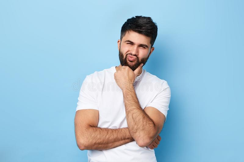 Young frowning man with thoughtful expression posing to the camera royalty free stock photo