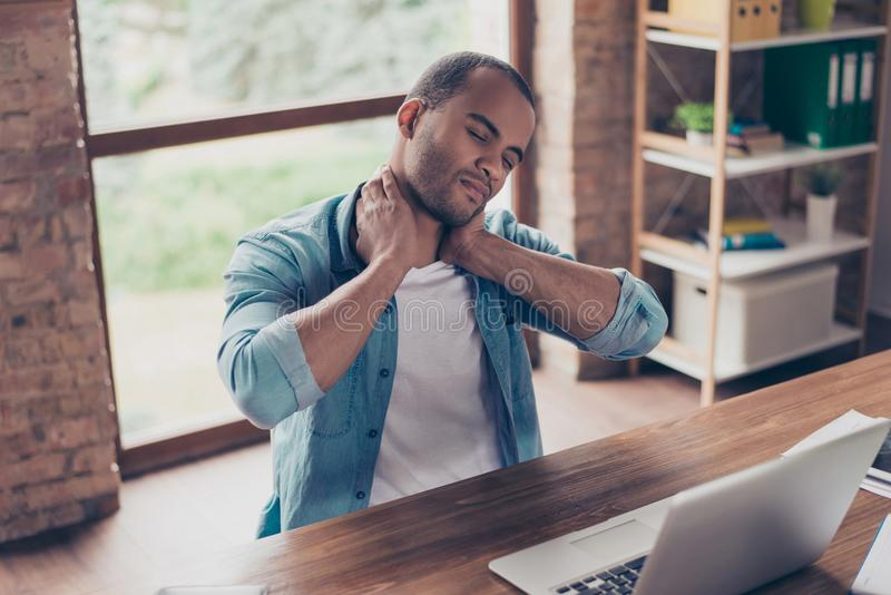 Young frustrated afro american freelancer is having a strong pain in neck. He is at home office, sitting at his modern work royalty free stock image