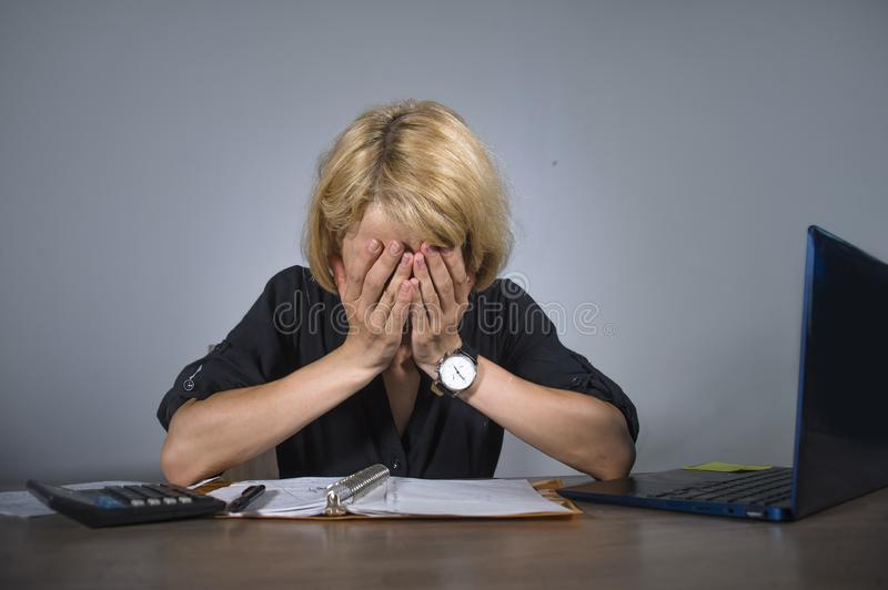 Young frustrated and stressed business woman crying sad at office desk working with laptop computer overwhelmed by paperwork workl. Oad covering her face royalty free stock photo