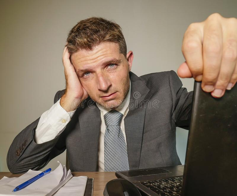 Young frustrated and stressed businessman in suit and tie working overwhelmed at office laptop computer desk suffering headache royalty free stock photography