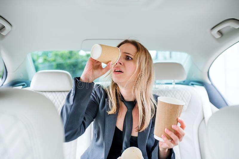 Young frustrated woman with empty paper glasses sitting in car. stock photo