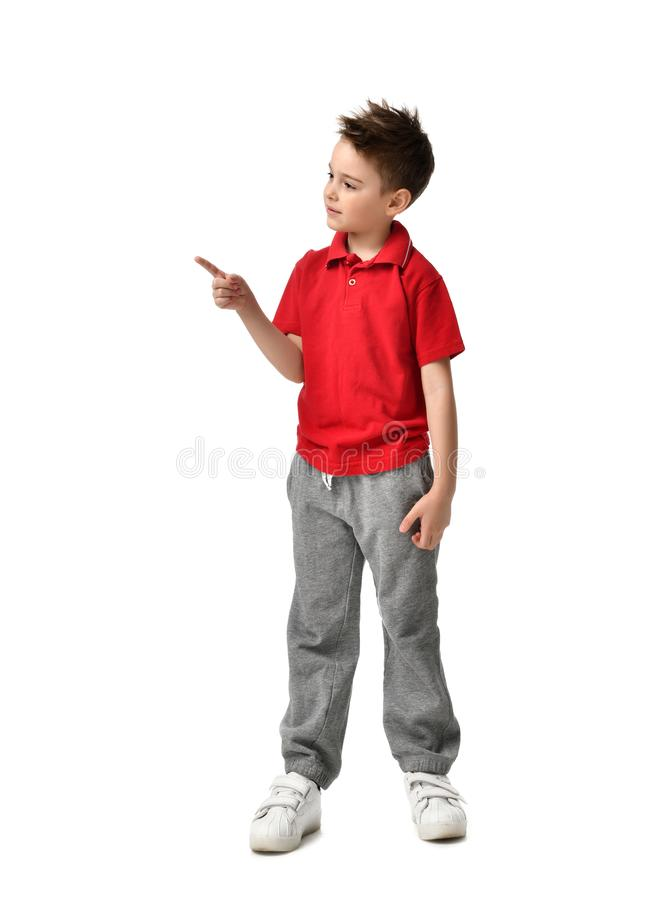 Young full body boy kid in red polo t-shirt standing pointing one finger at the corner isolated on white. Background royalty free stock photography