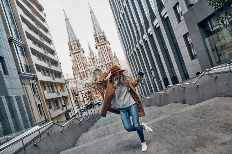 Young and full of energy. Full length of attractive young woman listening music and dancing while spending carefree time in the city stock photos