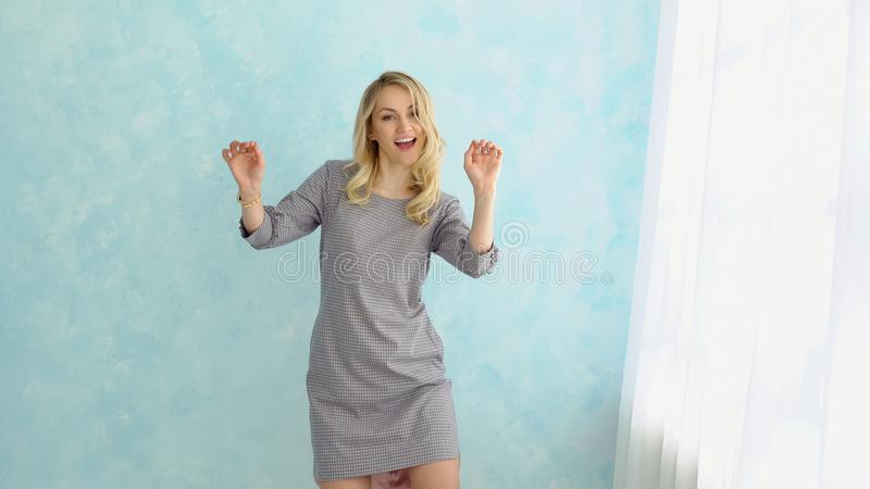 Young fun beautiful woman in a gray dress is dancing next to the window. royalty free stock images