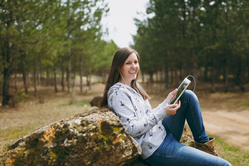 Young fun laughing beautiful woman in casual clothes with earphones sitting on stone using tablet pc computer in city. Park or forest on green blurred royalty free stock photos