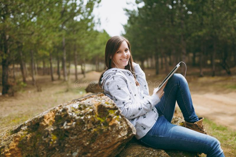 Young fun smiling beautiful woman in casual clothes with earphones sitting on stone using tablet pc computer in city. Park or forest on green blurred background royalty free stock image