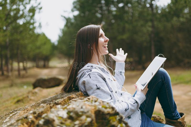 Young fun smiling beautiful woman in casual clothes with earphones sitting on stone using tablet pc computer in city. Park or forest on green blurred background stock images