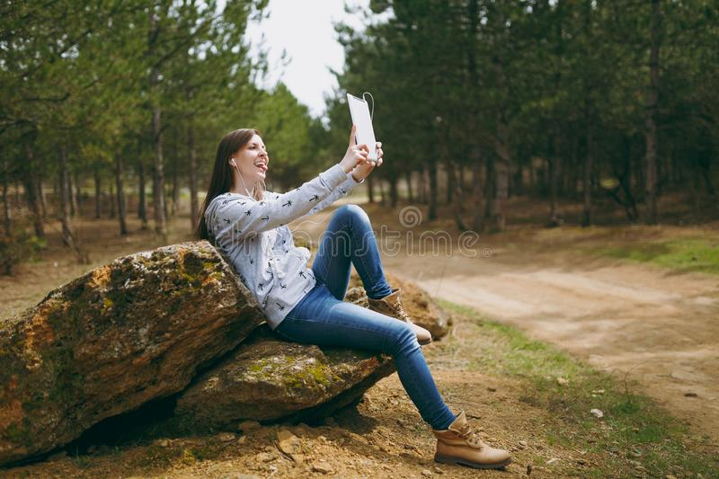 Young fun smiling woman in casual clothes with earphones sitting on stone using and doing selfie on tablet pc computer. In city park or forest on green stock images