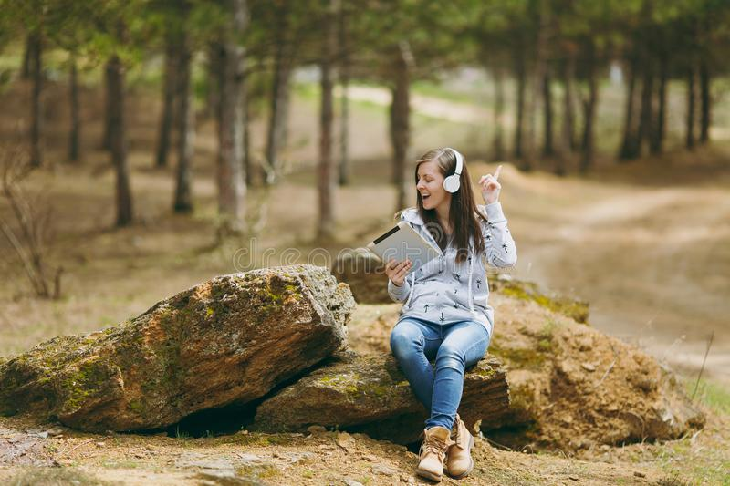 Young fun smiling woman in casual clothes sitting on stone listening music with headphones and tablet pc computer in. City park or forest on green background stock images