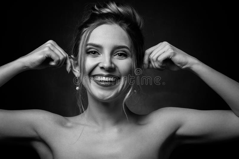 Woman show ears. Young fun woman on black background, shows her ears, grimacing, monochrome stock image