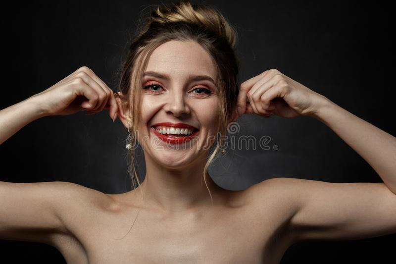 Woman show ears. Young fun woman on black background, shows her ears, grimacing stock photo