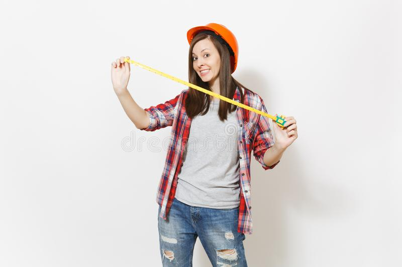 Young fun woman in casual clothes, protective construction orange helmet holding toy measure tape isolated on white stock image