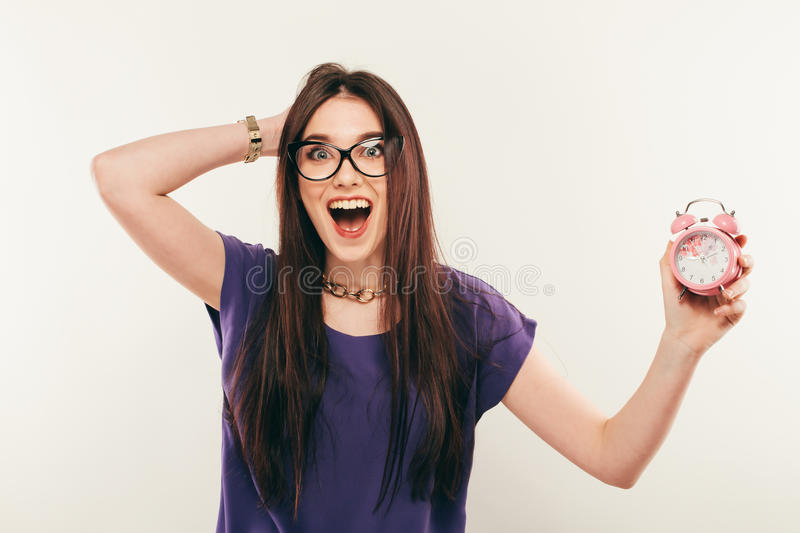 Young fun woman in glasses with alarmclock. Emotion smile stock image