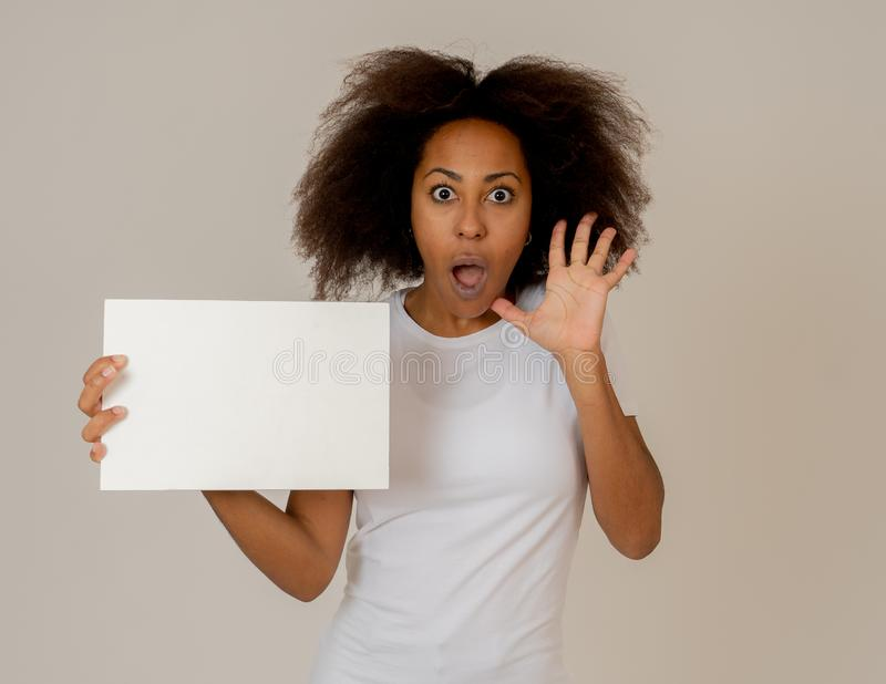 Young funny african american woman holding blank board add looking surprised and happy stock photography