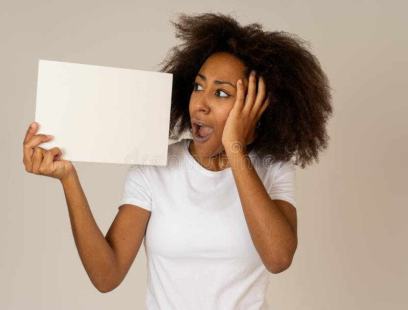 Young funny african american woman holding blank board add looking surprised and happy royalty free stock image