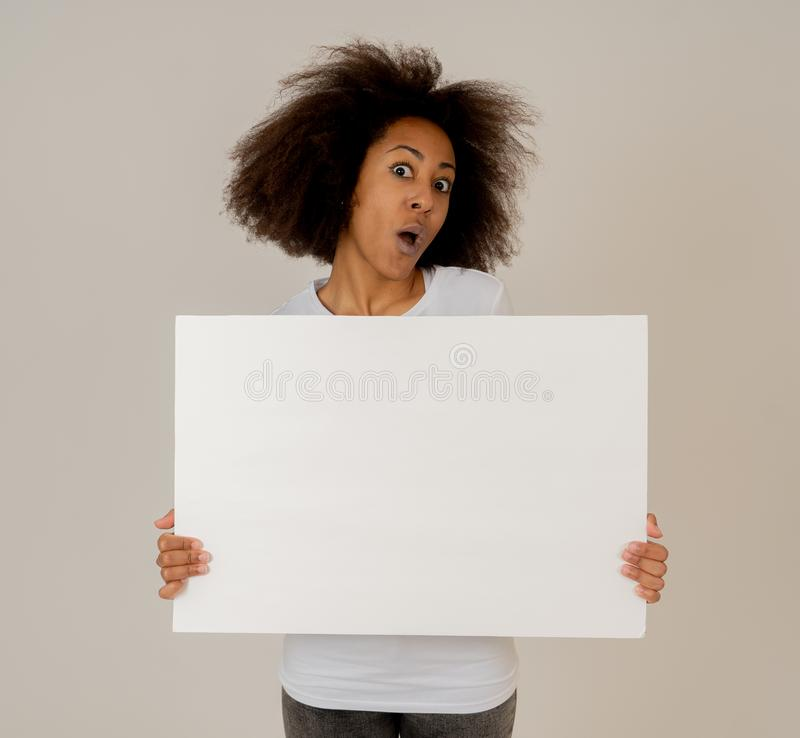 Young funny african american woman holding blank board for advertisement looking excited stock images