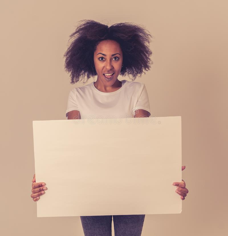 Young funny african american woman holding blank board for advertisement looking excited royalty free stock photos