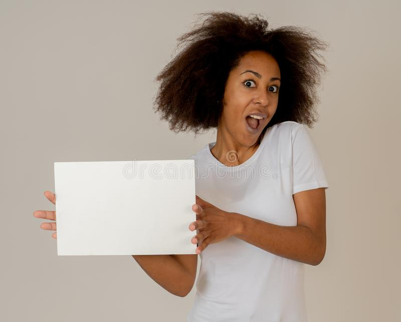 Young funny african american woman holding blank board for advertisement looking excited royalty free stock image