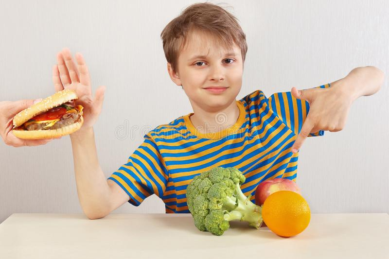 Young funny boy in a striped shirt at the table refuses hamburger in favor of fruit and vegetables on white background royalty free stock photography