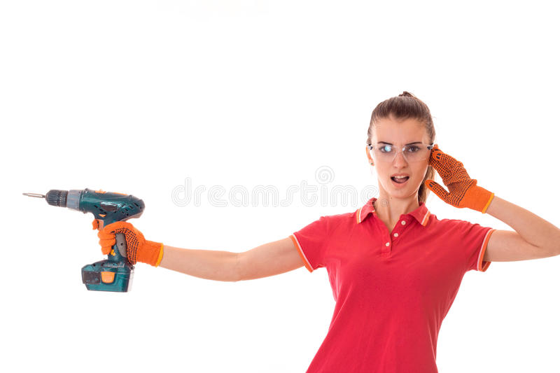 Young funny brunette woman builder in uniform with glasses and drill in her hands make reovations isolated on white stock photography