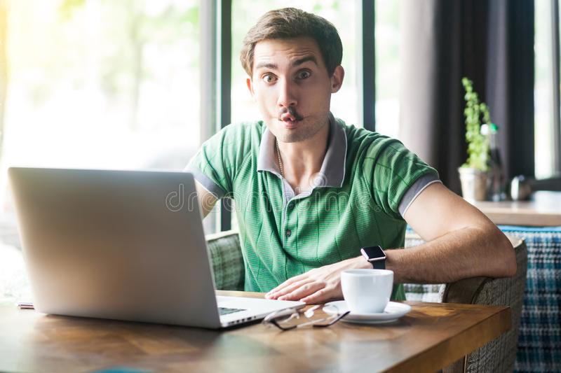 Young funny businessman in green t-shirt sitting and working on laptop and looking at camera with fish lips gesture crazy face stock photography