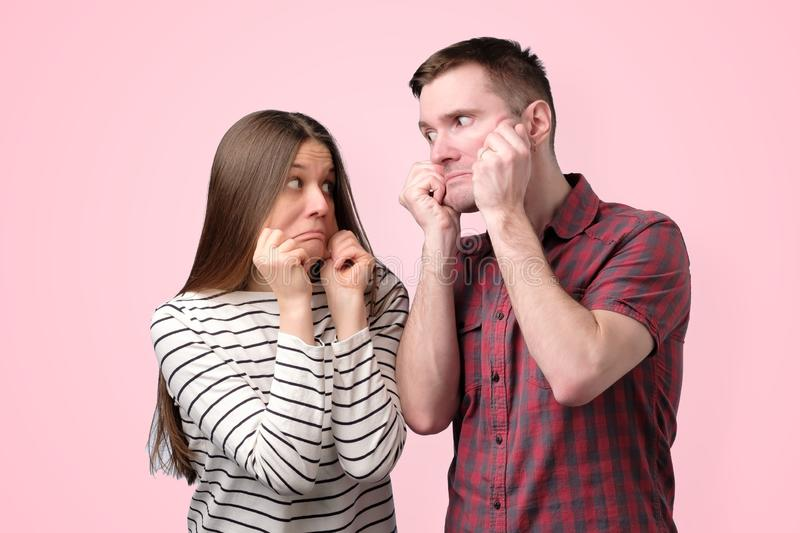 Young funny caucasian couple stretching skin on cheeks making strange grimace stock photography
