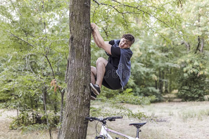 Young funny caucasian man climbs up to the tree with fair or horror, white bicycle stands down below. White wireless earphones, ca royalty free stock photography