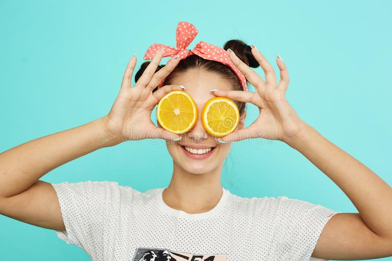 Young funny girl with pink bow on her head holds orange slices on place of her eyes on the blue background in the studio royalty free stock photo