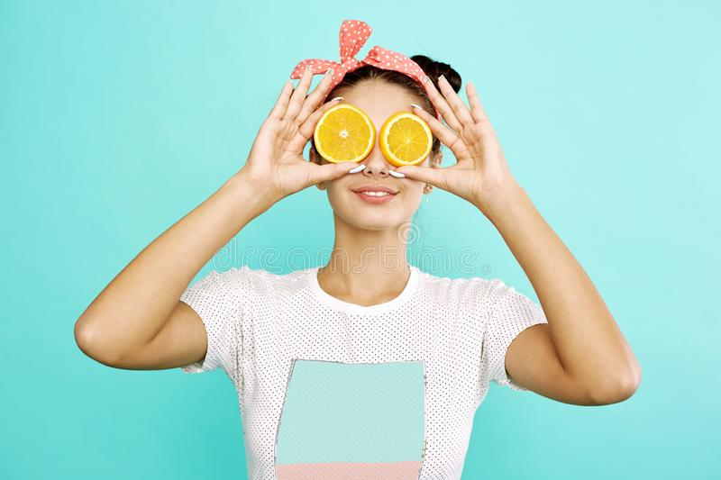 Young funny girl with pink bow on her head holds orange slices on place of her eyes on the blue background in the studio royalty free stock photography