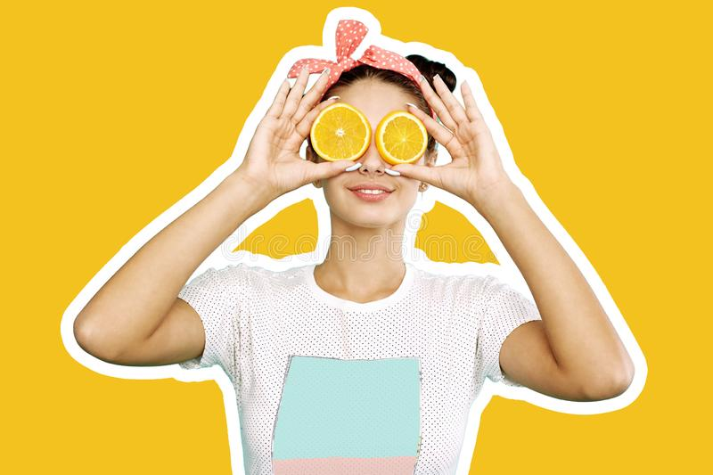 Young funny girl with pink bow on her head holds orange slices on place of her eyes on the orange background royalty free stock photos