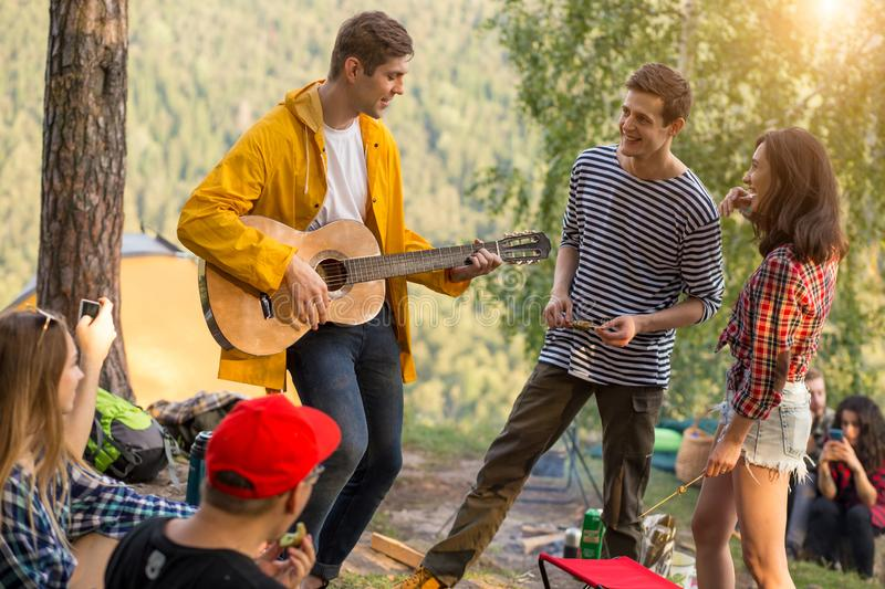Young funny guy performing his song to a friends while resting outdoors royalty free stock photos