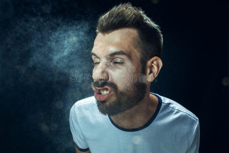 Young handsome man with beard sneezing, studio portrait royalty free stock photos