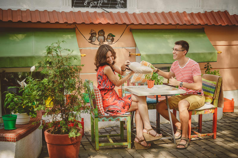Young funny happy loving couple sitting at street open-air cafe and fighting with pillows outdoors. Pillow fight. stock photo