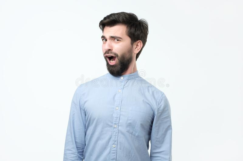 Young funny hispanic man with black beard is shocked and suprised. stock images