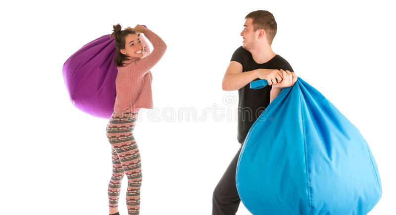 Young funny male and female fighting with beanbag chairs royalty free stock image