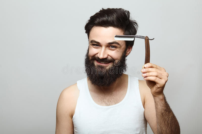Young funny man guy with beard showing razor blade stock photos