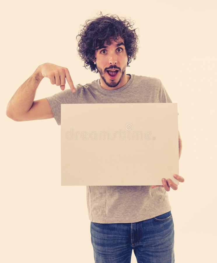 Young funny man holding blank board for advertisement. Millennial men pointing at white billboard royalty free stock image