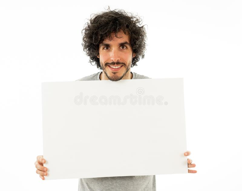 Young funny man holding blank board for advertisement. Millennial men pointing at white billboard royalty free stock photo